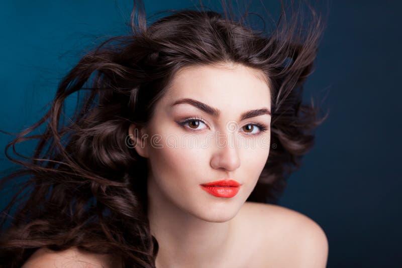 Alyona, cara séria com olhos marrons, fundo azul foto de stock royalty free