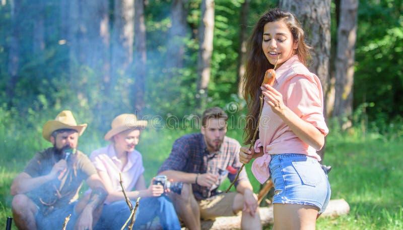 Alza del fin de semana Comida campestre con los amigos en bosque cerca de la hoguera Compañía que tiene fondo de la naturaleza de fotografía de archivo