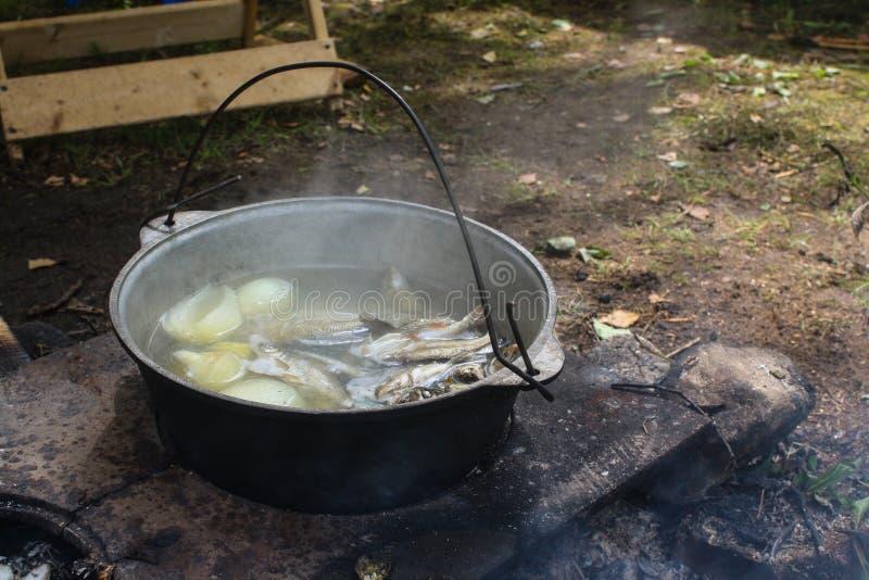 alza pesque la sopa en un pote en el fuego foto de archivo