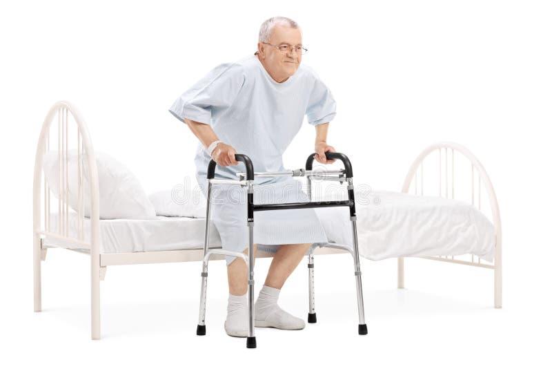 Alzarsi paziente maturo dal letto con il camminatore fotografie stock