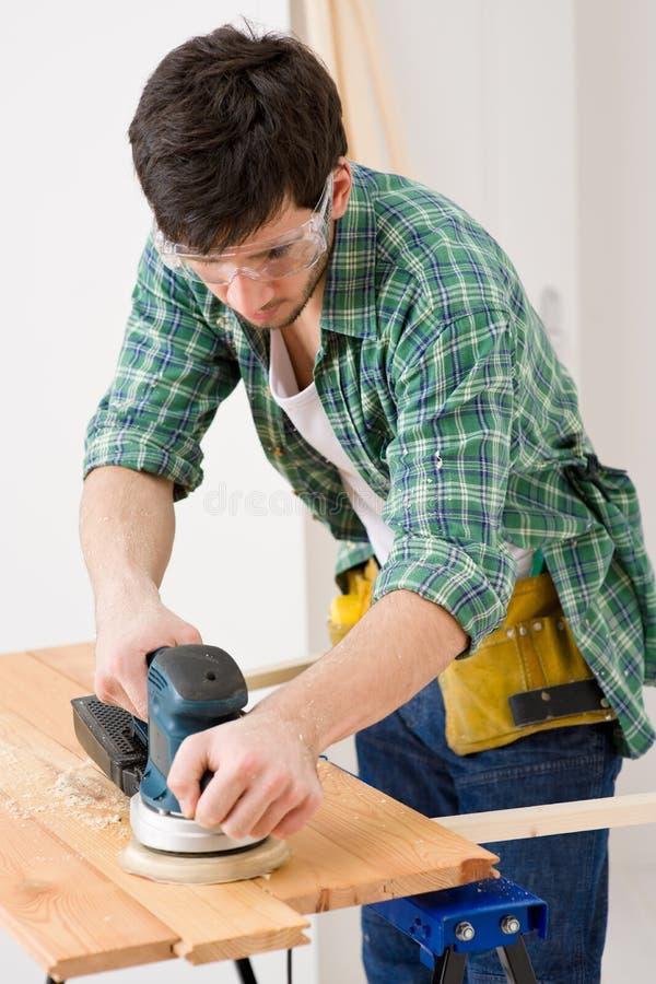 Amélioration de l'habitat - bricoleur sablant l'étage en bois photographie stock libre de droits