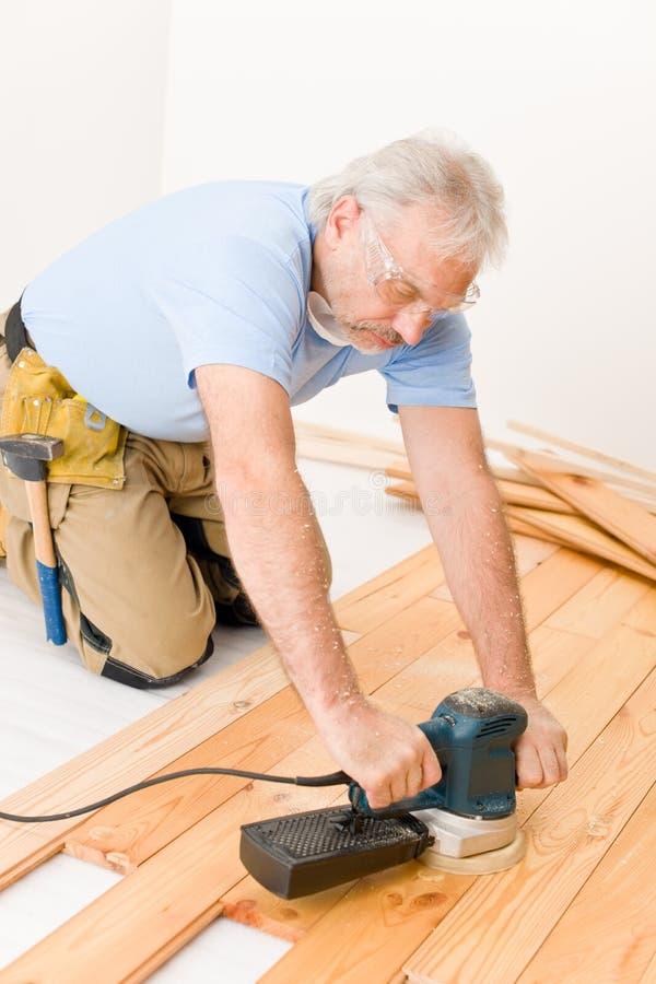 Amélioration de l'habitat - bricoleur sablant l'étage en bois images libres de droits