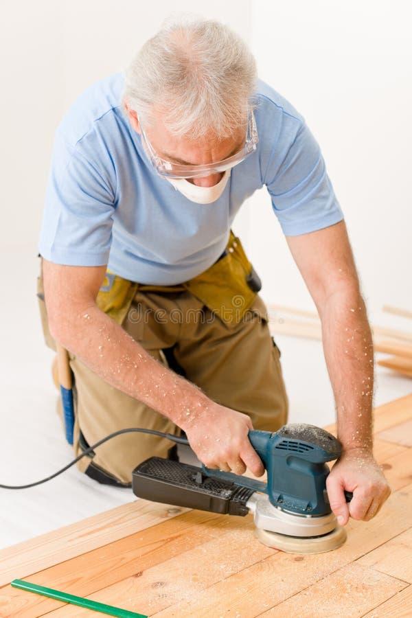 Amélioration de l'habitat - bricoleur sablant l'étage en bois photos stock