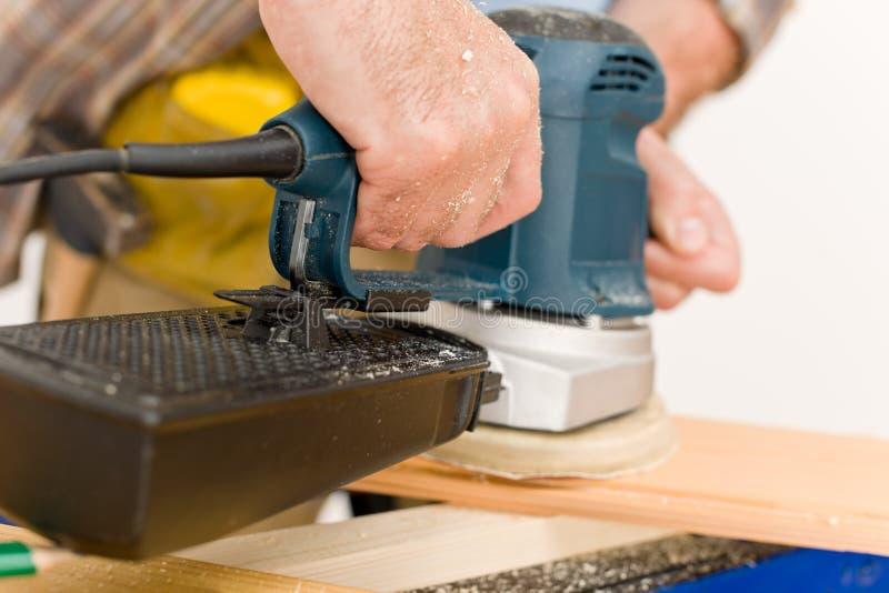 Amélioration de l'habitat - bricoleur sablant l'étage en bois image stock