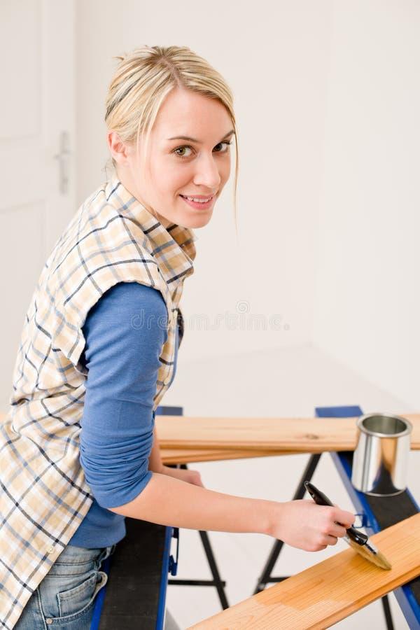 Amélioration de l'habitat - femme peignant la planche en bois image stock