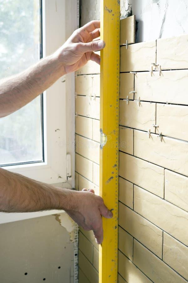 Amélioration de l'habitat - le bricoleur mesure la rectitude du mur photos libres de droits