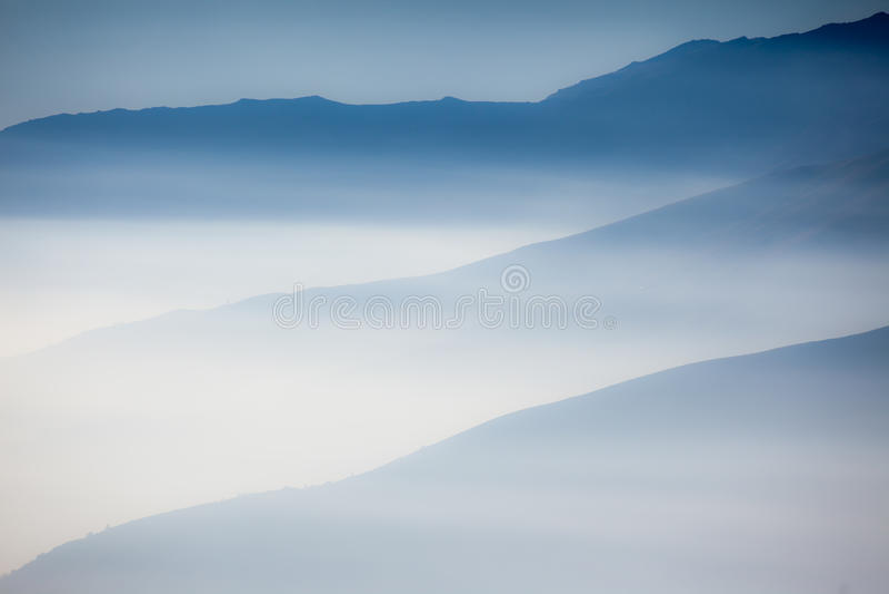 Aménagez en parc avec des couches colorées de montagnes et de brume dans le vall photographie stock libre de droits