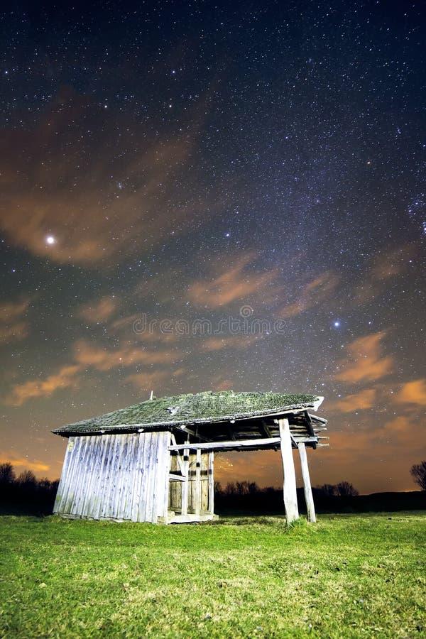 Aménagez en parc avec la cabane en bois de vintage sous la lumière d'étoiles photographie stock libre de droits