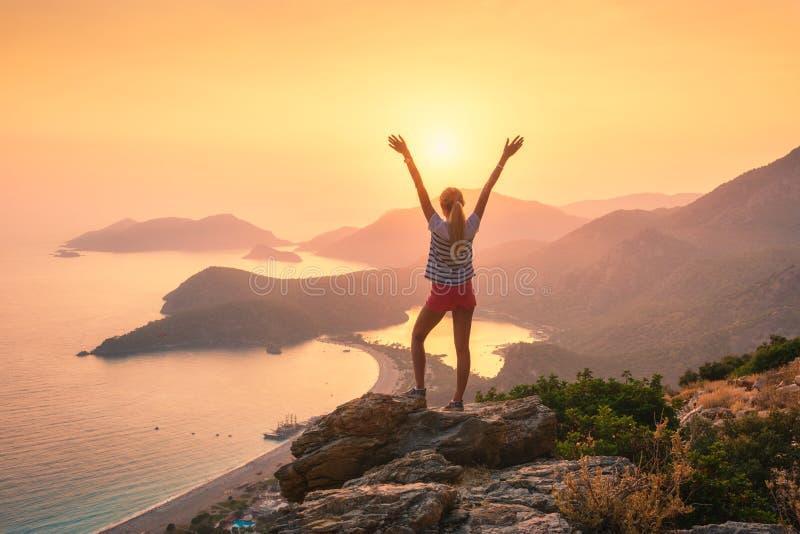 Aménagez en parc avec la femme, la mer, les arêtes de montagne et le ciel orange images stock