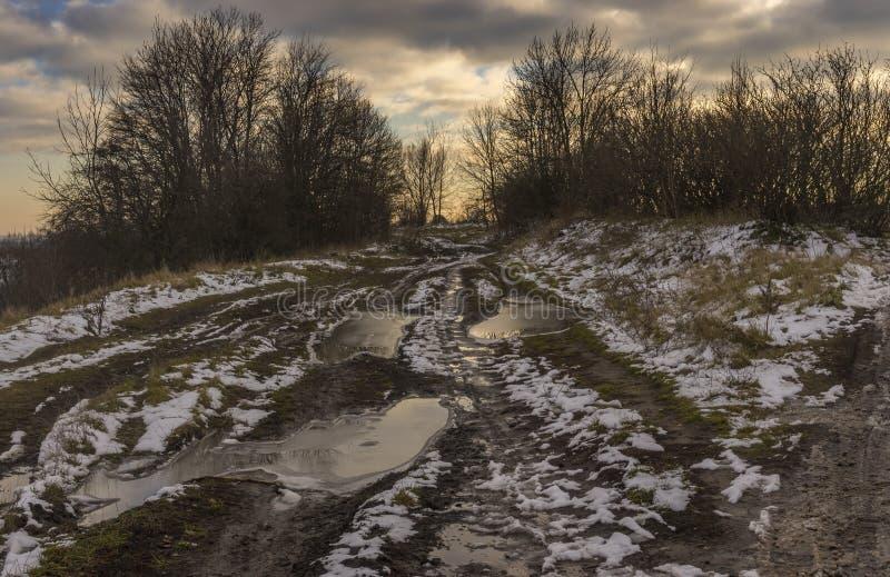 Aménagez en parc avec la route extrêmement sale menant au petit village ukrainien Shpilivka dans l'oblast de Sumskaya, Ukraine image stock