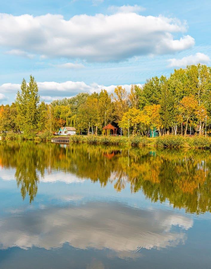 Aménagez en parc avec le lac, le ciel nuageux, et les arbres reflétés symétriquement dans l'eau Lac salt Sosto Nyiregyhaza, Hongr photo stock