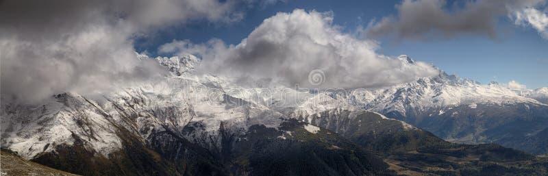 Aménagez en parc, les crêtes couronnées de neige des montagnes de Svaneti dans la vue de nuages de la vallée, Svaneti, la Géorgie photos stock