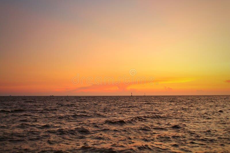 Aménagez en parc, vue de mer à la belle lumière orange du coucher du soleil A Il y a des cargos passant  image libre de droits