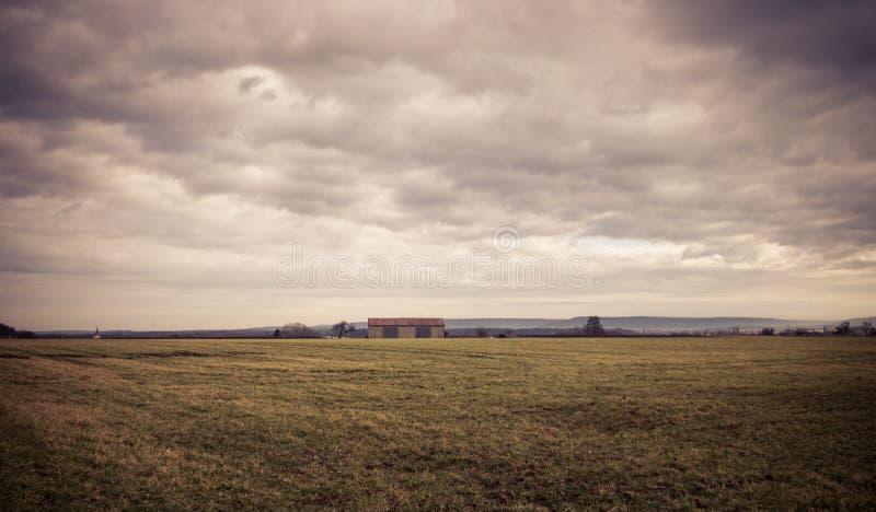 Aménagez la vue en parc à une grange sous le ciel nuageux photo stock