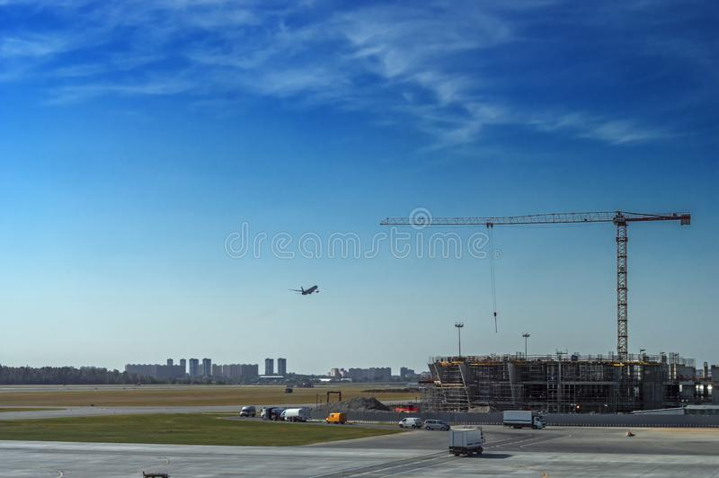 Aménagez le grand aéroport en parc moderne de chantier de construction avec la grands grue de construction et avions de vol sur l photographie stock libre de droits