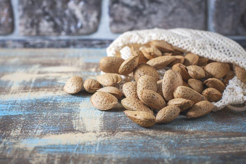 Amêndoas em um saco do algodão reusável em uma tabela de madeira Eco-pacote, conceito zero do desperdício Conceito da amêndoa com imagem de stock
