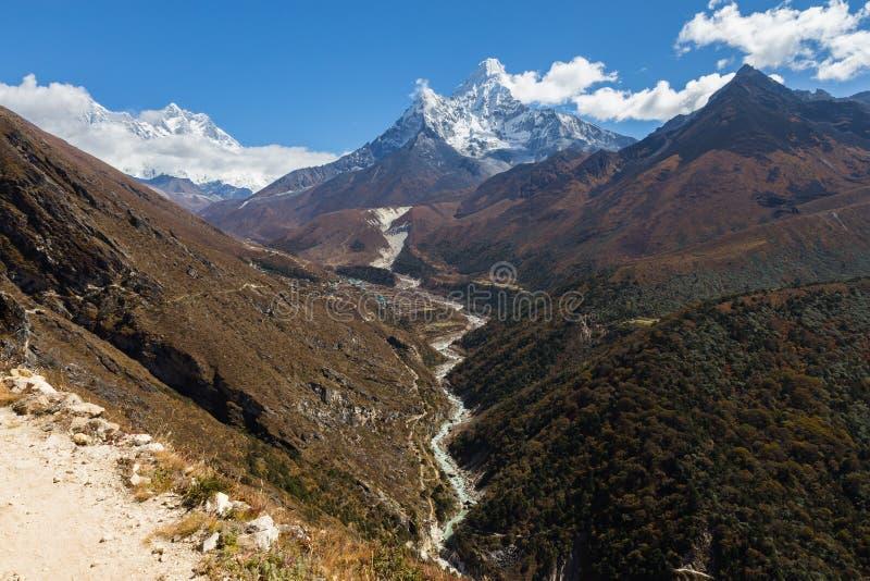 Ama Dablam bergsnö når en höjdpunkt, floden för den Pangboche bykanjonen arkivbild