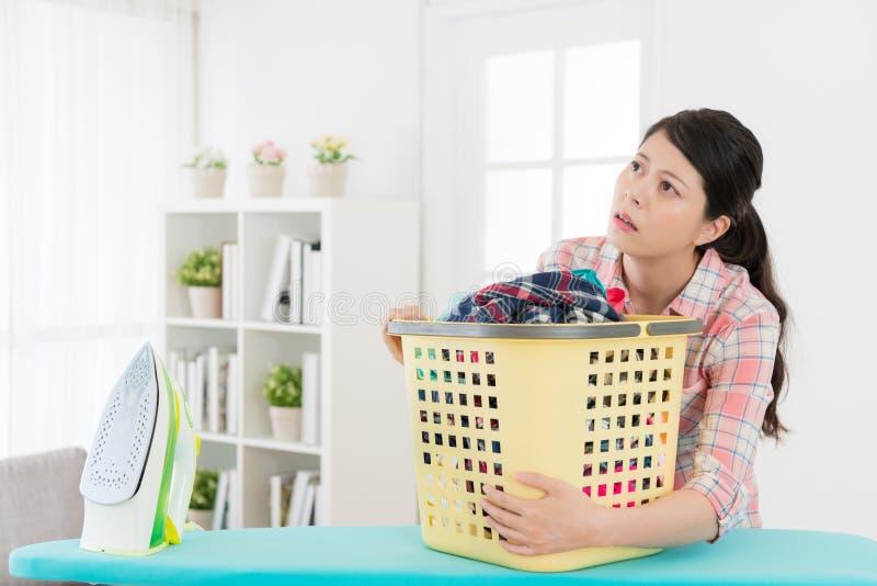 Ama de casa atractiva que sostiene la cesta de lavadero imagen de archivo