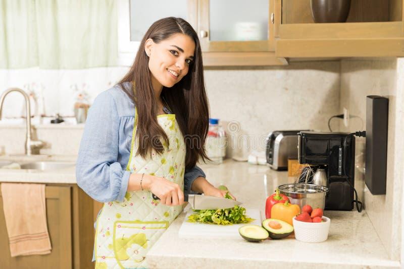 Ama de casa bonita que cocina en una cocina fotos de archivo libres de regalías