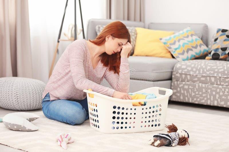 Ama de casa cansada con la cesta llena de ropa foto de archivo libre de regalías