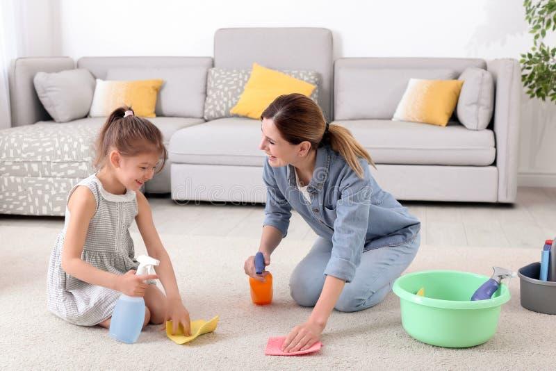 Ama de casa con la alfombra de la limpieza de la hija foto de archivo libre de regalías