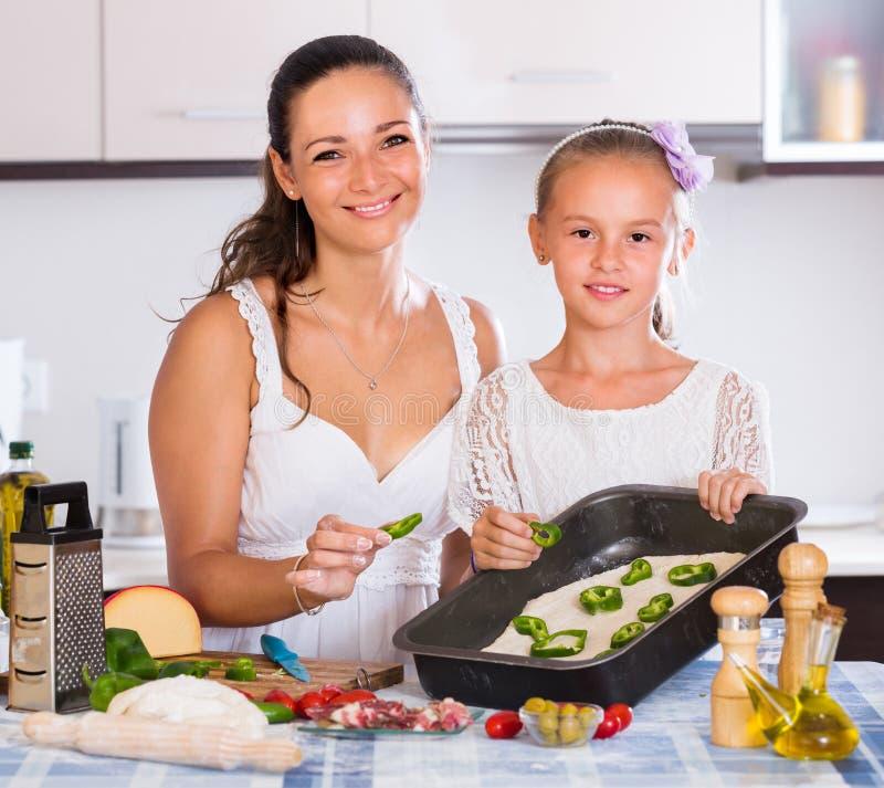 Ama de casa con la muchacha que cocina la pizza foto de archivo