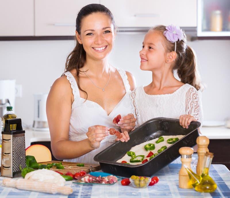 Ama de casa con la muchacha que cocina la pizza fotos de archivo