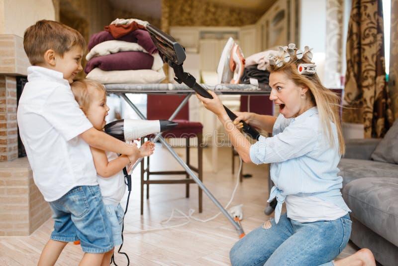 Ama de casa con los niños que juegan en casa junto imágenes de archivo libres de regalías