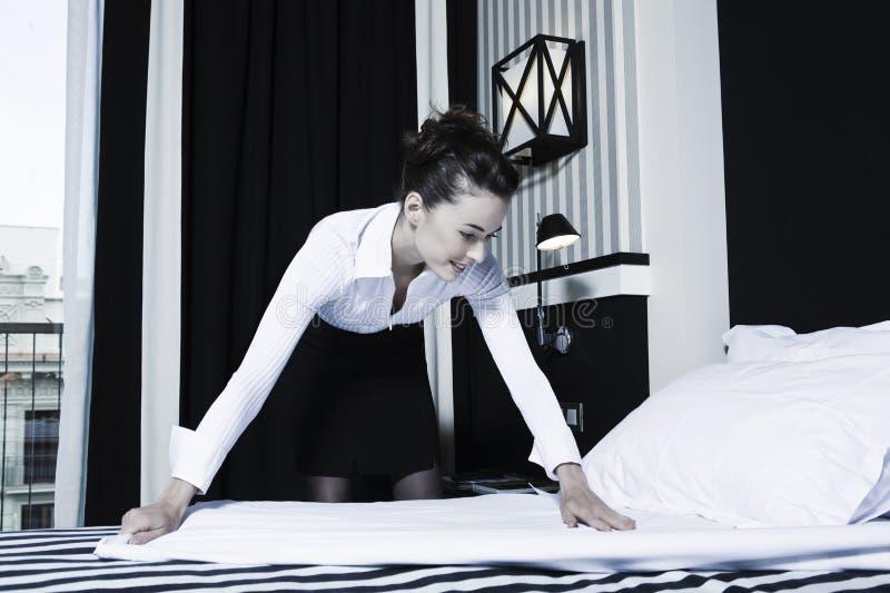 Ama de casa de la mujer que hace la cama en un dormitorio del hotel fotografía de archivo