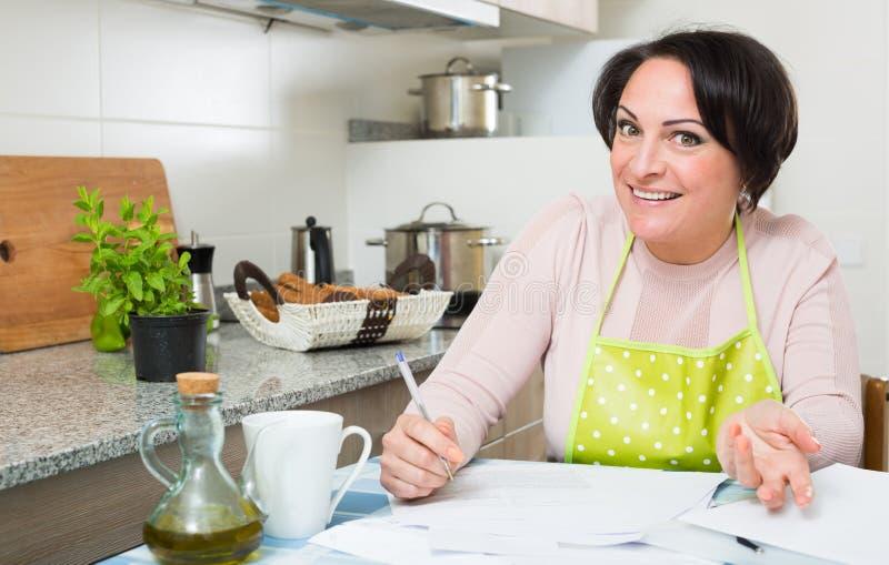 Ama de casa feliz con los papeles de actividades bancarias en cocina imagen de archivo