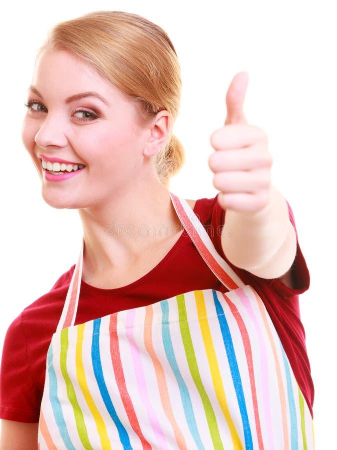 Ama de casa feliz en el delantal de la cocina que muestra golpe encima de la muestra de la mano foto de archivo libre de regalías