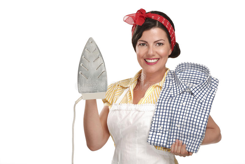 Ama de casa hermosa feliz de la mujer que plancha una camisa imagenes de archivo