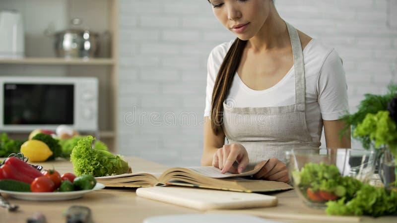 Ama de casa hermosa que busca receta tradicional de la familia en la abuelita que cocina el libro fotografía de archivo