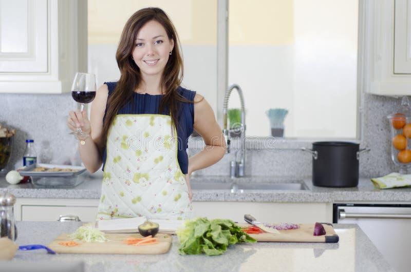 Ama de casa hermosa que cocina la cena imagen de archivo libre de regalías