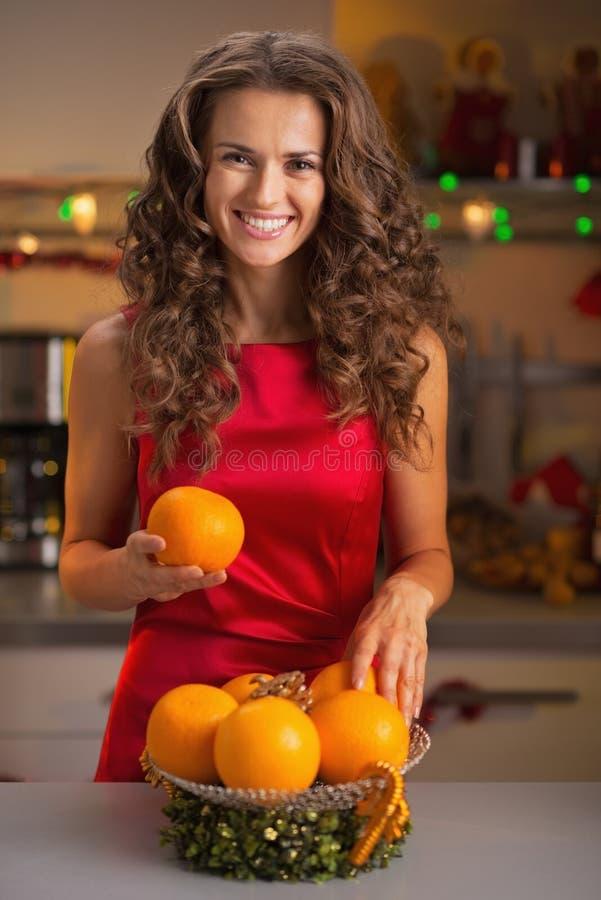 Ama de casa joven feliz que adorna la placa de la Navidad con las naranjas fotos de archivo libres de regalías