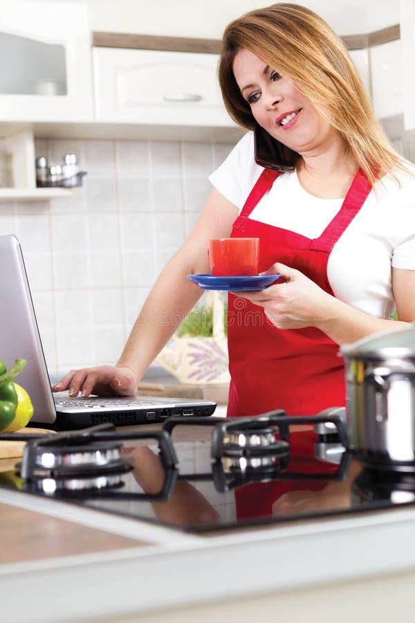 Ama de casa joven moderna que usa un ordenador portátil mientras que cocina fotografía de archivo