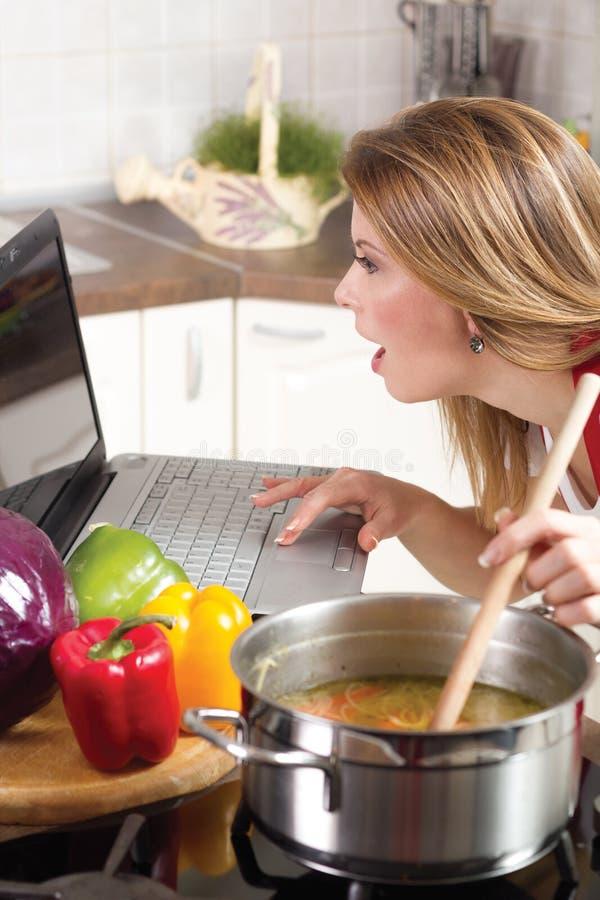 Ama de casa joven moderna que usa un ordenador portátil mientras que cocina imagenes de archivo