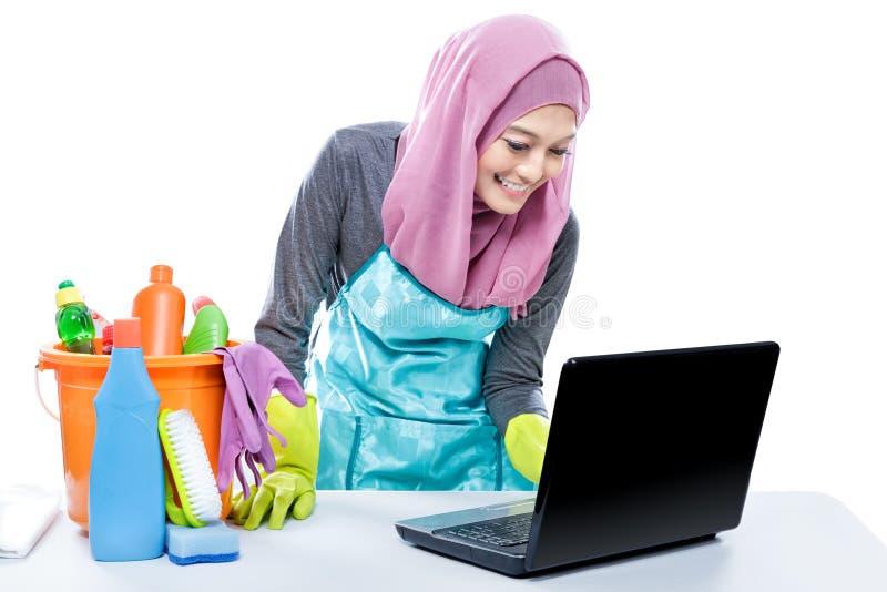 Ama de casa joven polivalente que usa el ordenador portátil mientras que limpia la tabla fotografía de archivo