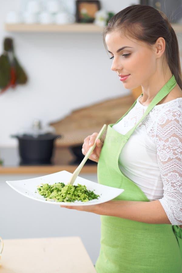 Ama de casa de la mujer joven que cocina en la cocina Concepto de comida fresca y sana en casa imagen de archivo libre de regalías