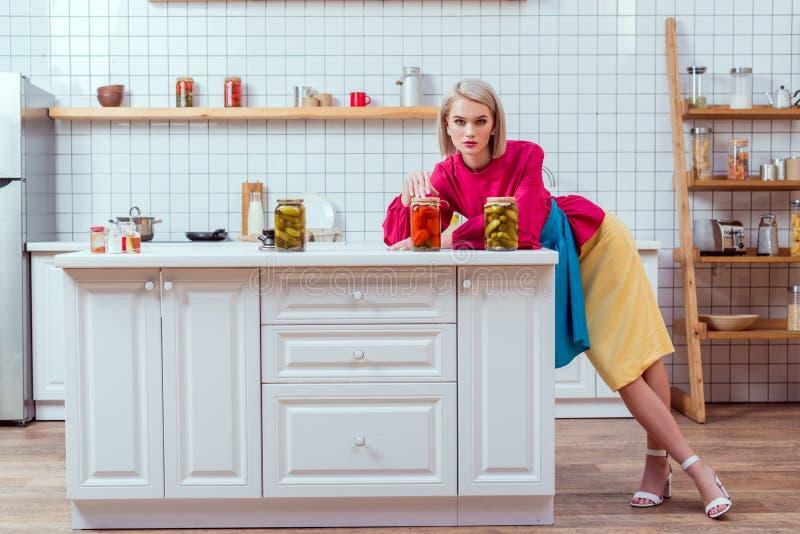 ama de casa de moda hermosa con las latas de verduras conservadas en vinagre en contador imágenes de archivo libres de regalías