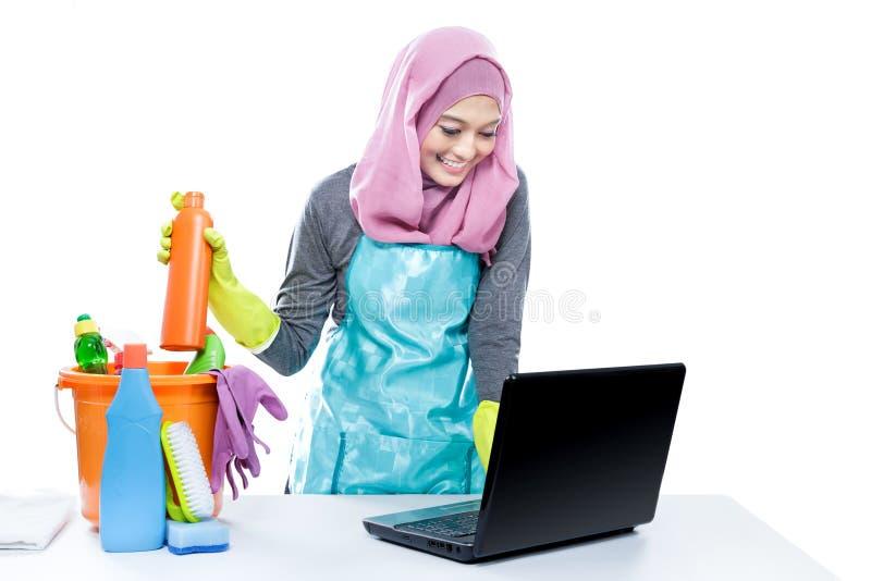 Ama de casa polivalente que usa el ordenador portátil mientras que limpia la casa fotografía de archivo libre de regalías