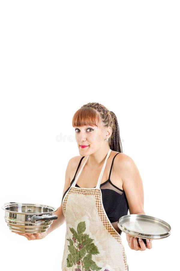 Ama de casa preciosa en el delantal que intenta cocinar fotografía de archivo