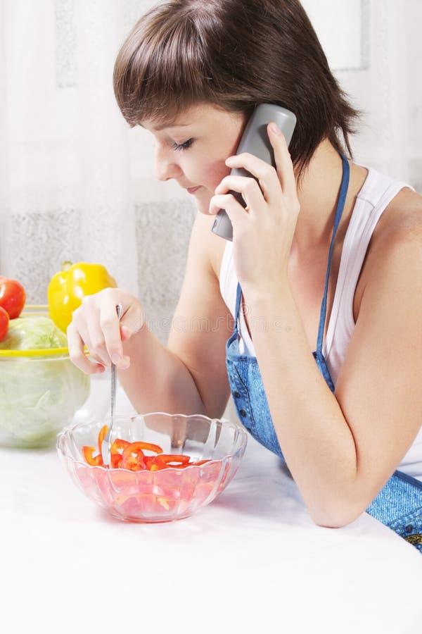 Ama de casa que habla en el teléfono que come la ensalada fresca fotos de archivo