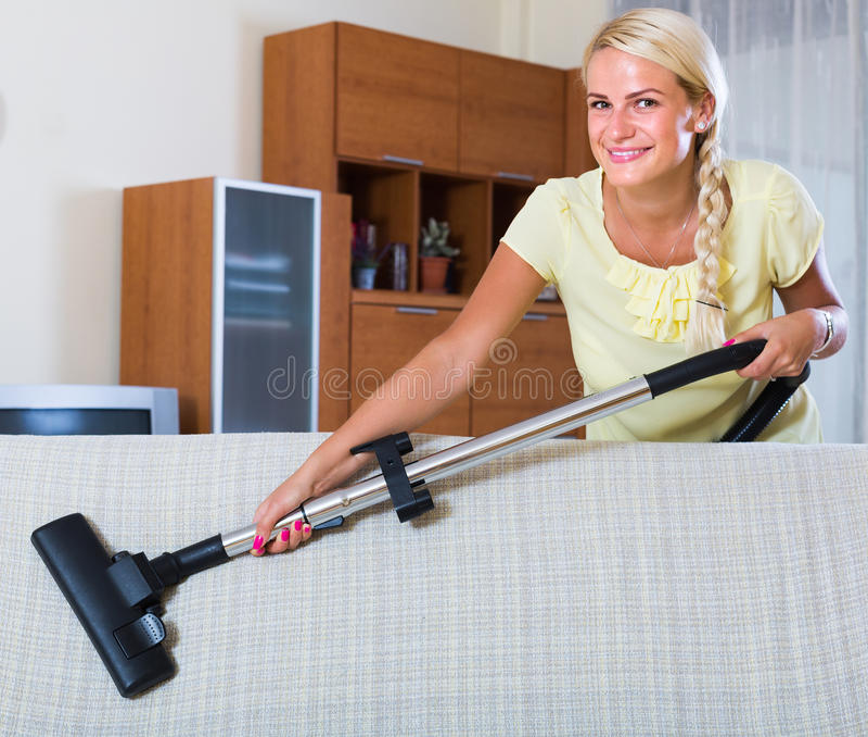 Ama de casa que limpia con la aspiradora en casa imagen de archivo libre de regalías