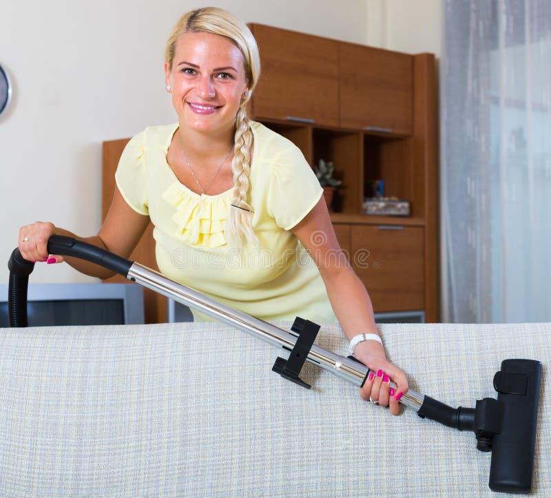 Ama de casa que limpia con la aspiradora en casa fotografía de archivo