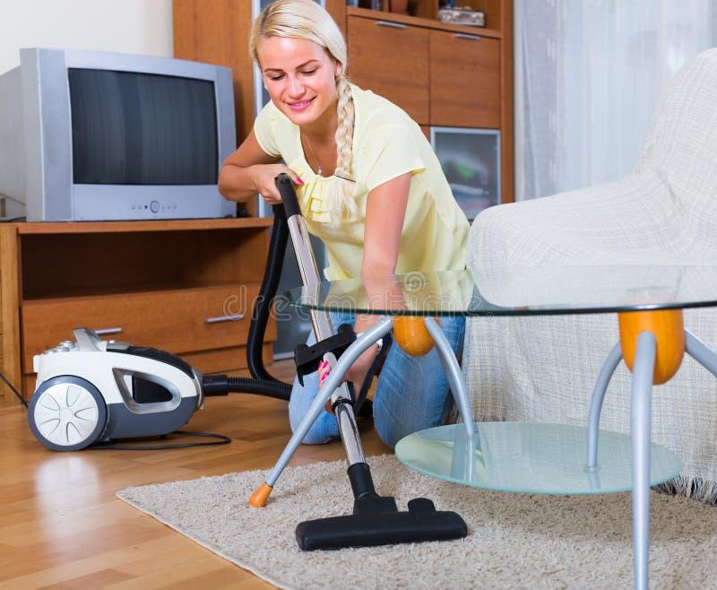 Ama de casa que limpia con la aspiradora en casa imagenes de archivo