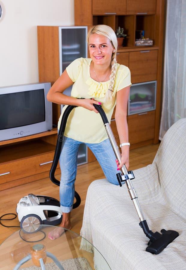 Ama de casa que limpia con la aspiradora en casa fotografía de archivo libre de regalías