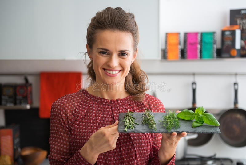 Ama de casa que muestra las hierbas frescas de las especias en los submarinos de piedra foto de archivo libre de regalías