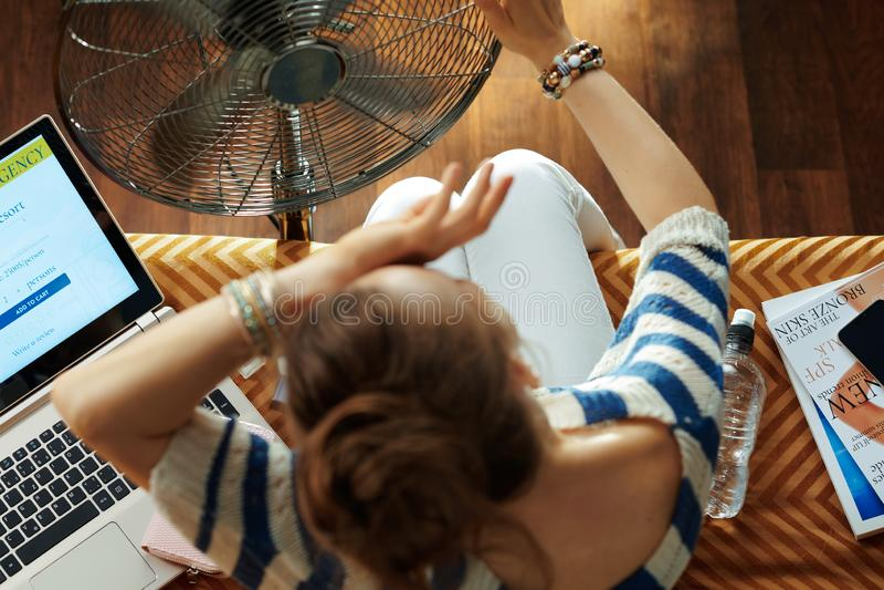 Ama de casa que se refresca abajo usando rato de la fan para sufrir de calor imagen de archivo libre de regalías