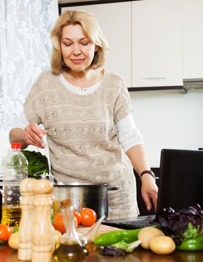 Ama de casa que usa el cuaderno mientras que cocina en cocina imagen de archivo